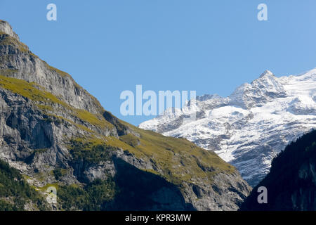 The rocky mountains seen from Grindelwald. Snow is visible on distant peaks like in winter, and the rocks of high - Stock Image