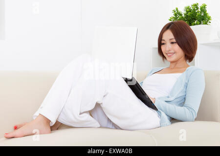 Young woman sitting on sofa and using laptop with smile, - Stock Image