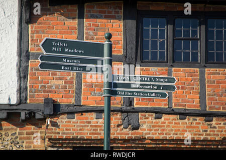 Tourist information and direction sign in Henley-on-Thames, Oxfordshire in front of medieval house with exposed timbers. - Stock Image