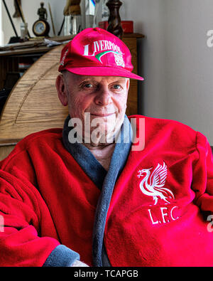 Happy senior man wearing Liverpool football club colours after Club wins the 2019 Campions League. Liverpool fan at home - Stock Image