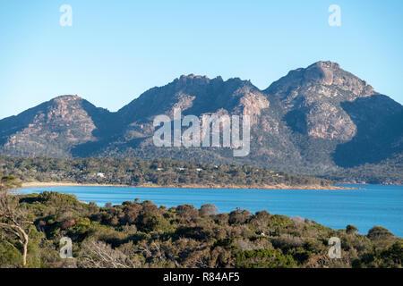 Hazard mountain range, Freycinet National Park, Tasmania taken from Coles Bay on a sunny day with blue sky - Stock Image