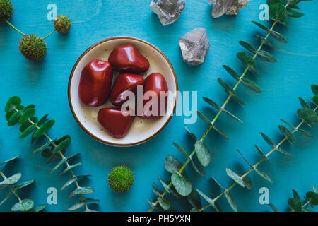 Red Jasper with Quartz and Eucalyptus on Turquoise Table - Stock Image
