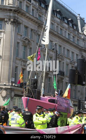 London, UK. 19th Apr, 2019. Police seen next to a pink boat during the demonstration.Environmental activists from Extinction Rebellion movement occupy London's Oxford Circus for a 5th day. Activists parked a pink boat in the middle of the busy Oxford Circus road junction blocking the streets and causing traffic chaos. Credit: Keith Mayhew/SOPA Images/ZUMA Wire/Alamy Live News - Stock Image