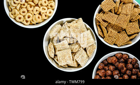 Selection of Bowls of Healthy Eating Breakfast Cereal Including Shredded Wheat Chocolate Nesquik Shreddies and Cheerios - Stock Image