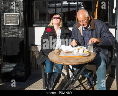 Man and a woman eating al fresco outside a café in Whitby North Yorkshire, woman enjoying the autumn sunshine - Stock Image