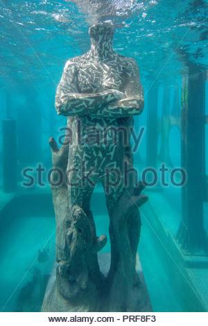 Underwater Coralarium statue with arms crossed in Maldives - Stock Image