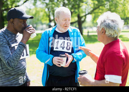 Active senior men friends finishing sports race and drinking coffee in sunny park - Stock Image
