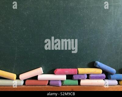 Chalkboard and coloured chalks - Stock Image