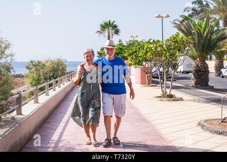 People couple walking enjoying the outdoor leisure activity near the beach - happyu retirement old senior caucasian man and woman concept living toget - Stock Image