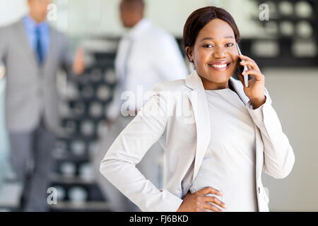 cheerful afro American businesswoman talking on cell phone in office - Stock Image
