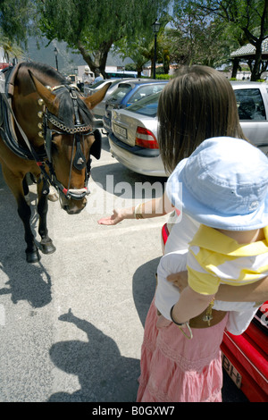 Mother holding toddler, reaching out her hand to a stroke horse, in the streets of in Mijas Pueblo, Costa del Sol, - Stock Image
