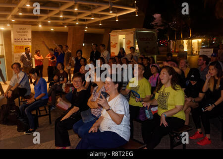 Enthusiastic audience clapping and cheering karaoke singer along the Esplanade walk in Singapore - Stock Image
