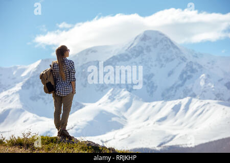 Woman with backpack stands on viewpoint and looks at mountains - Stock Image