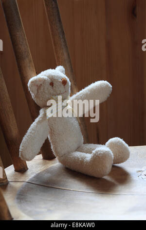 A small teddy bear is sitting on a wooden chair. - Stock Image
