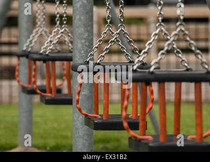 Row of swing seats at a local play park or children's playground provided by the local council for children - Stock Image