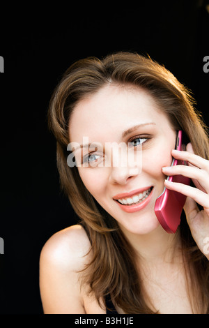 Close up portrait of young adult female talking on cell phone and smiling - Stock Image