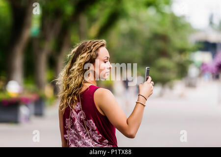 A beautiful young woman walking down a street near a university campus messaging using video on her smart phone; Edmonton, Alberta, Canada - Stock Image