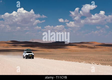 4x4 truck on the dusty desert road to the Namib Naukluft Nat. Park, used by tourists driving to the famous red sand dunes at Sossusvlei, Namibia. - Stock Image