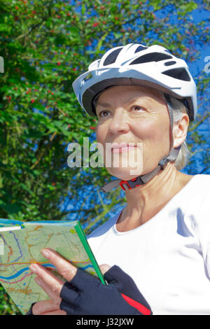 Senior woman outdoors in the summer sun with bicycle helmet, protective gloves, white t-shirt and map, looking for - Stock Image