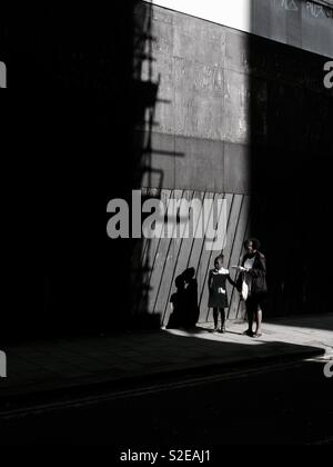 Woman and daughter standing in a shaft of light - Stock Image