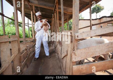 Rwandan meat producer poses with one of his pig pens, Kigali, Rwanda - Stock Image