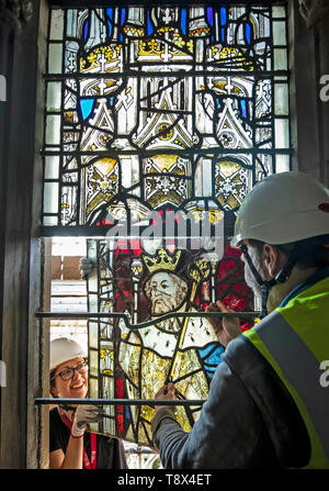 Conservation manager Nick Teed (right) and conservator Zoe Harrigan (left) remove a stained glass windows panel during the first phase of work to protect 600-year-old stained glass windows at York Minster. The work is part of an 11 year, ??11m conservation and restoration project at the cathedral. - Stock Image