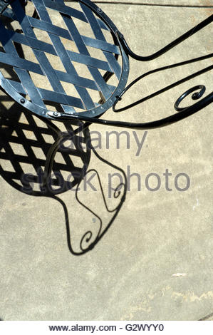 Black metal patterned outdoors chair, with shadow. Australia. - Stock Image