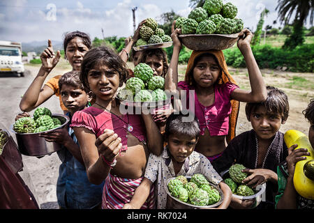 Children selling fruits on highway to earn money - Stock Image
