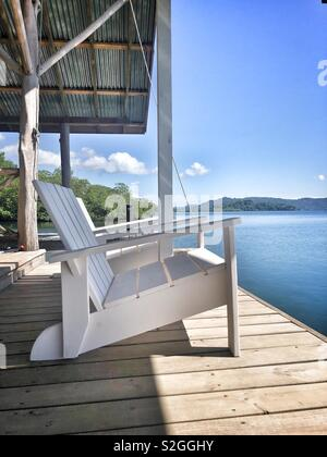 White wooden chair on a wooden verandah looking out into blue water - Stock Image
