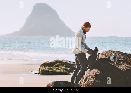 Man packing his backpack with sea view beach travel in Norway active lifestyle vacations outdoor adventure trip - Stock Image