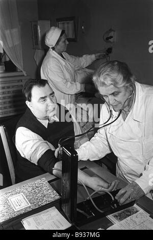 Retired blacksmith Sergeyev of the Leningrad Metalworks seeing the doctor at the company outpatient clinic 1959 - Stock Image