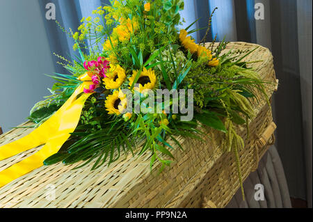 A flower arrangement on a braided coffin in a mortuary - Stock Image