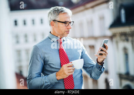 A mature businessman with coffee and smartphone standing on a terrace in an office in city, texting. - Stock Image