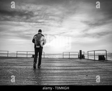 Backpacker tourist standing at sea on old wooden bridge. Promenade at pier in the sea. - Stock Image