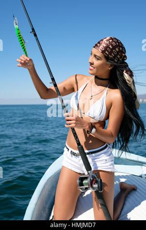 Young attractive hispanic woman checking the plastic lure on her fishing rod - Stock Image