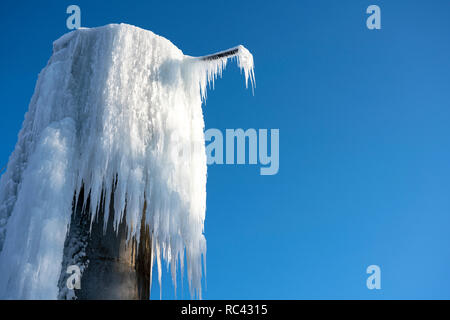 Frozen water tower, hanging huge frozen streams of water - Stock Image