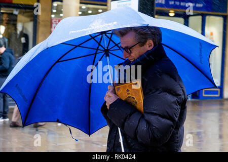 Bath, UK. 8th February, 2019. As storm Eric brings gales and heavy rain across the UK a pedestrian in the centre of Bath is pictured carrying an umbrella as he braves the heavy rain and wind. Credit: Lynchpics/Alamy Live News - Stock Image