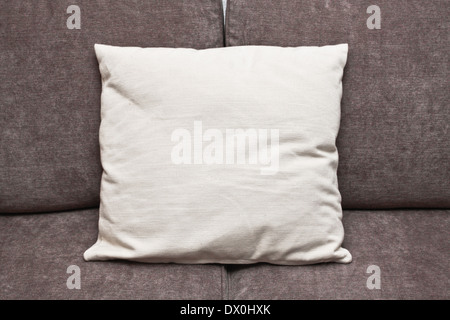 An off-white cushion on a brown sofa - Stock Image