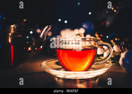 Tea cup with tea pot on the table. Cozy tea party at home - Stock Image