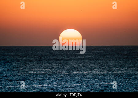 Sunset or sunrise moment over the ocean with sun touching the horizon line on the water - romantic and touristic concept for travel vacation backgroun - Stock Image
