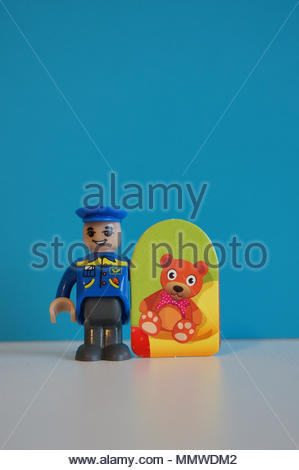 Plastic toy mail man holding a card with bear illustration in soft focus - Stock Image