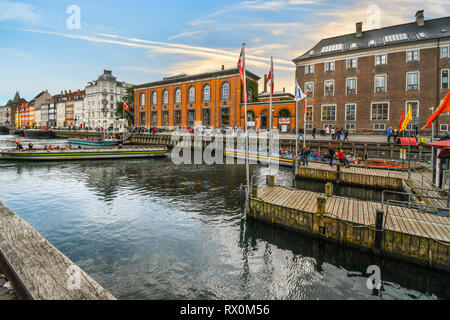 A tour boat turns around on the Nyhavn canal in Copenhagen Denmark - Stock Image