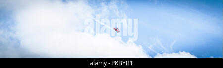 Little red airplane with propeller flying among the skies with smoke on the tail in panorama - Stock Image