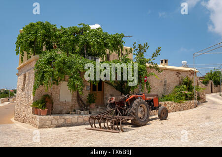 A tractor parked outside a house in Ineia village, Paphos region, Cyprus. - Stock Image