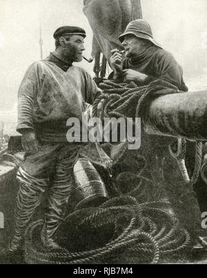 Two fishermen on a fishing smack, Suffolk, England, surrounded by coils of rope. - Stock Image