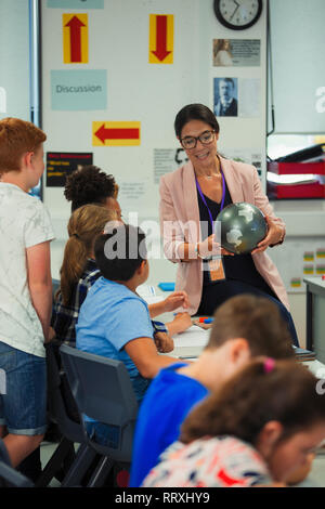 Female geography teacher with globe teaching lesson in classroom - Stock Image