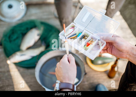 Fisherman holding box with fishing tackles during the picnic outdoors, close-up view - Stock Image