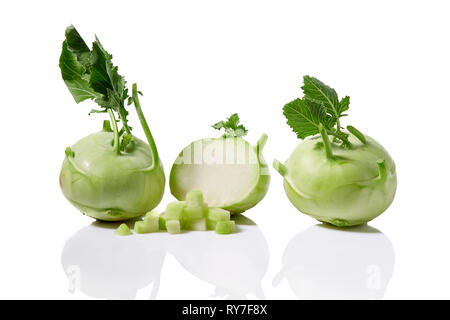 Fresh kohlrabi with with leafy stems still attached on white background - Stock Image