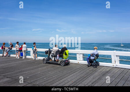 Disabled woman in wheelchair and handicapped persons in duo two person mobility scooter watching sailing boats at sea from jetty - Stock Image