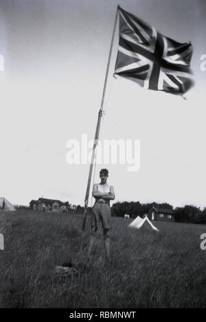 1930s, historical, British boy scout at an overseas summer camp standing outside in a grassy field next to a tall pole with a union jack flag on, Dublin, Ireland - Stock Image